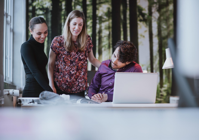 3 workers around a desk